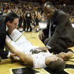 Pat Beckmann Associate Director of Sports Medicine (L) and Missouri Tigers head basketball coach Mike Anderson stand over Justin Stafford after Stafford injured his knee in the first half against the Colorado Buffalos at the Mizzou Arena in Columbia, Missouri on February 24, 2010.   UPI/Bill Greenblatt