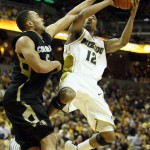 Missouri Tigers Marcus Denmon (12) moves past Colorado Buffalo's Marcus Relphorde for the layup and two points in the first half.   UPI/Bill Greenblatt