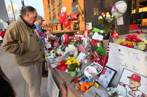 Fans inspects some of the items that have been left around the Stan Musial statue outside of Busch Stadium in St. Louis on January 20, 2013. Musial died at the age of 92 in