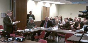 Senator David Pearce (standing, left) opens the hearing of the Joint Education Committee.