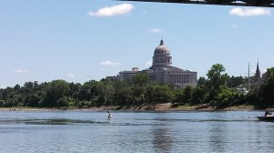 A kayaker travels on the Missouri River past the State Capitol at Jefferson City.