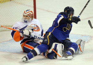 St. Louis Blues Jaden Schwartz falls on the legs of New York Islanders goaltender Anders Nilsson of Sweden during a goal in the first period at the Scottrade Center in St. Louis on December 5, 2013. UPI/Bill Greenblatt