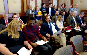 Low-wage workers Amy Jenawine and Patrick Leeper (bottom left) fill out witness forms before testifying in favor of a bill that would allow Missourians to vote on a minimum wage increase.