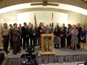 Chris Kelly (at podium) and other lawmakers and organizations' representatives urge Governor Jay Nixon to sign criminal code legislation.