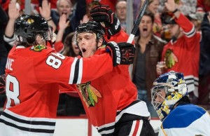 Patrick Kane (88) celebrates with Jonathan Toews as Ryan Miller looks ahead early in game three (NHL.com)