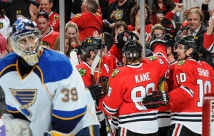 Patrick Kane celebrates a goal with his teammates as Ryan Miller looks on in the second period. (NHL photos)