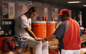St. Louis Cardinals starting pitcher Michael Wacha looks at his arm in the dugout with pitching coach Derek Lilliquest after being drilled by a foul ball off the bat of teammate Matt Adams in the sixth inning against the Arizona Diamondbacks at Busch Stadium in St. Louis on May 21, 2014. Wacha left the game. UPI/Bill Greenblatt