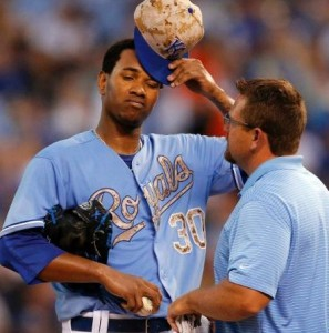 Yordano Ventura is met by a team trainer in the third inning. (photo/MLB)