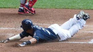 Carlos Gomes slides into home with a run for Milwaukee.  The Brewers hold onto first place through the All-Star break. (photo/MLB)