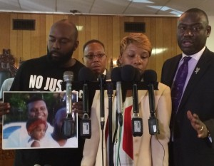 Michael Brown, Senior, holds a picture of Michael Brown at a press conference with Brown's mother, Lesley McSpadden and attorney Benjamin Crump (right).  (photo courtesy; Jessica Machetta)
