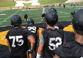 Defensive players look on through drills on the first day of fall camp.
