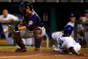 Lorenzo Cain slides past Kurt Suzuki with the tying run in the eighth inning. (photo/MLB)