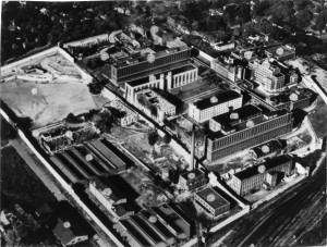 An aerial view of Missouri State Penitentiary after the Sept. 22, 1954 riot.  Labeled are:  1. An Outside Warehouse, 2. Ball Field, 3. Gas Chamber, 4. License Plate Factory 5. Clothing Factory, 6. I-Hall, 7. Shoe Factory, 8. Soap Factory, 9. Power House, 10. (number not placed on image), 11. Recreation Building, 12. Vocational Building, 13. Tabacco Shop, 14. F & G Halls, 15. B & C Halls, 16. Dining Hall, 17. A-Hall, 18. Maintenance Building, 19. E-Hall, 20. J & K Halls, 21. Machine Shop, 22. Furniture Factory, 23. Commisary & Cold Storage, 24. Hospital, 25. Garage, 26. Administration Building, 27. Chapel (Courtesy; Missouri State Archives and Mark Schreiber)