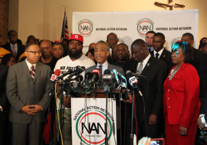 The Rev. Al Sharpton makes his remarks as Michael Brown Sr. (hat) and Brown family attorneys listen in during a press conference in Ferguson, Missouri on November 25, 2014. After the verdict was read in the Michael Brown Jr. shooting case looting, riots and fires broke out in the area on November 24, 2014.   UPI/Bill Greenblatt