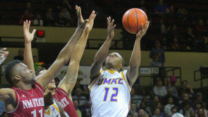 Martez Harrison attempts a shot over two New Mexico State defenders (photo/UMKC Athletics)