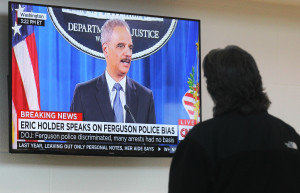 A visitor to the Ferguson, Missouri Community Center stops to watch U.S. Attorney General Eric Holder deliver his comments on the problems with the Ferguson Police Departent in Ferguson, Missouri on March 4, 2015. (Photo by BIll Greenblatt/UPI)