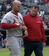 Matt Holliday is looked at by the team trainer after getting hit on the elbow