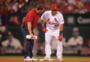 St. Louis Cardinals Matt Adams is examined by trainer Chris Conroy after pulling up after hitting a double against the Arizona Diamondbacks in the fifth inning at Busch Stadium in St. Louis on May 26, 2015. Photo by Bill Greenblatt/UPI