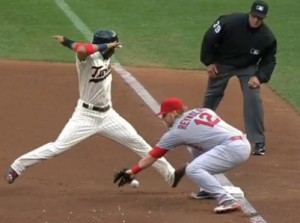 Mark Reynolds misplays a pickoff attempt leading to the Twins' first run of the game.