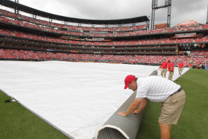 Busch Stadium grounds crew members place the tarp on the field for the third time before a game between the Kansas City Royals and the St. Louis Cardinals at Busch Stadium in St. Louis on June 14, 2015. The game was postponed due to rain. Photo by Bill Greenblatt/UPI