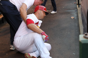 St. Louis Cardinals Matt Holliday is attended to by trainer Chris Conroy as he sits on the floor of the dugout after injuring his leg in the first inning against the Cincinnati Reds at Busch Stadium in St. Louis on July 29, 2015. Photo by Bill Greenblatt/UPI