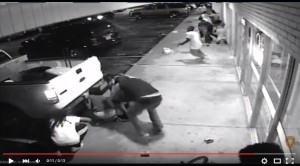 Police say this image shows Tyrone Harris, Junior holding a handgun (in white t-shirt, towards upper-right of image) shortly before he was shot by plainclothes officers. (screencap from video released by St. Louis County Police)
