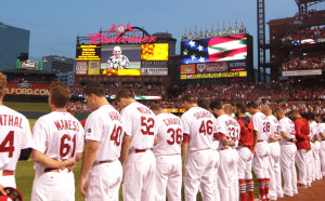 Members of the St. Louis Cardinals stand for a moment of silence for the late New York Yankee Yogi Berra before a game against the Cincinnati Reds at Busch Stadium in St. Louis on September 23, 2015. Berra, a member of the National Baseball Hall of Fame, was born in St. Louis and died at the age of 90 today.    Photo by Bill Greenblatt/UPI