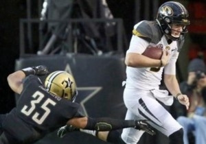 Drew Lock avoids the tackle of a Vandy player (photo/Mizzou Athletics)
