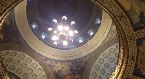 Works raise the chandelier in the Missouri Capitol rotunda back toward the dome after cleaning.