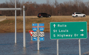 Traffic flows freely on Interstate Highway 44 as several traffic signs are still submurged in flood water from the Meramec River in Valley Park Missouri on January 1, 2016. Flooding statewide from three straight days of rain caused evacuations, road closures and fifteen deaths. Photo by Bill Greenblatt/UPI