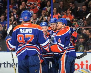 Members of the Edmonton Oilers gather after a goal (photo/NHL.com)