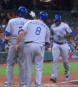 Lorenzo Cain is greeted at home plate by Alcides Escobar and Mike Moustakas