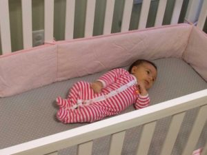 A baby in a crib with a bumper.  (photo credit; Washington University)