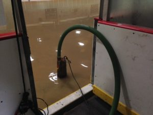 Maintenance workers pump out water inside the rink at Washington Park (photo/Bill Pollock)