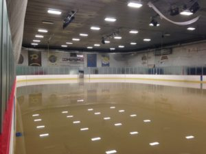 Lights reflect off the muddy water that covers the rink surface (photo/Bill Pollock)