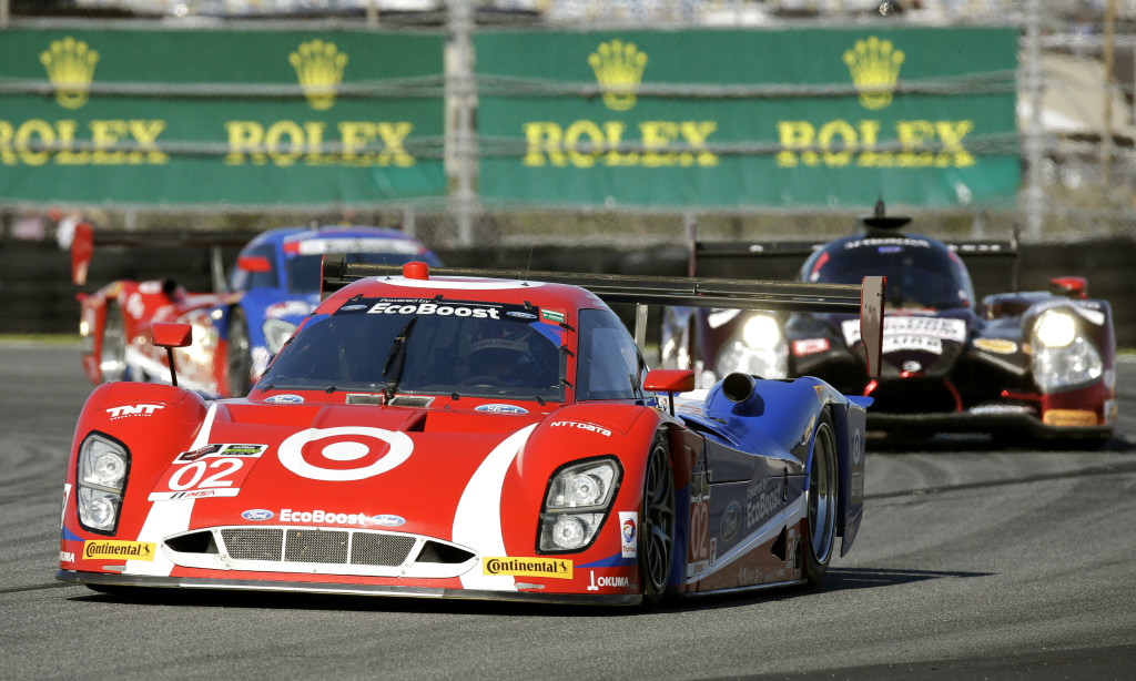 Scott Dixon (02), of New Zealand, leads Oswaldo Negri, Jr., right, of Brazil, and Scott Pruett, of the U.S. , back left, out of a turn during early laps of the IMSA 24 hour auto race at Daytona International Speedway, Saturday, Jan. 24, 2015, in Daytona Beach, Fla. (AP Photo/John Raoux)